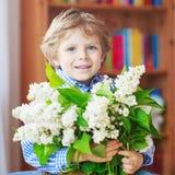 Menino pequeno adorável da criança com a flor lilás branca de florescência Fotografia de Stock