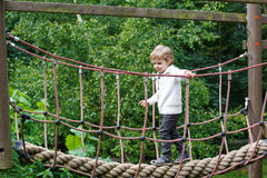 Menino pequeno bonito da criança que tem o divertimento com escalada no campo de jogos do mim Imagem de Stock