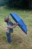Menino pequeno bonito que guarda o guarda-chuva azul na grama verde Fotos de Stock