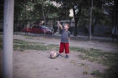 Menino pequeno com o futebol que mostra no céu Fotografia de Stock Royalty Free