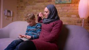 Menino pequeno concentrado que joga o jogo na tabuleta e em sua mãe muçulmana no hijab que acariciam o maciamente em casa video estoque