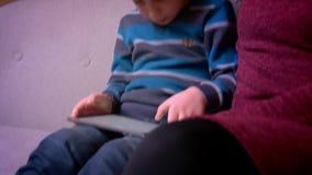 Menino pequeno concentrado que joga o jogo na tabuleta e em sua mãe muçulmana no hijab que senta-se próximo em casa filme