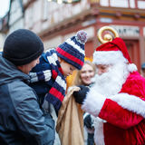 Menino pequeno da criança com pai e Santa Claus no mercado do Natal Foto de Stock