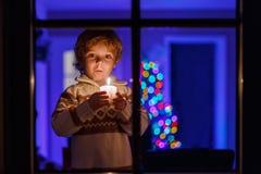Menino pequeno da criança que está pela janela no tempo e na posse do Natal Foto de Stock