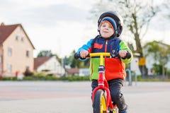 Menino pequeno da criança que tem o divertimento e que monta sua bicicleta Imagens de Stock Royalty Free