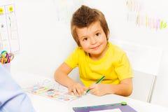 Menino pequeno de sorriso que colore as formas no papel imagem de stock