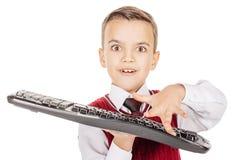 Menino pequeno do estudante com o teclado isolado no backgr branco do estúdio Imagens de Stock Royalty Free