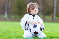 Menino pequeno do fã na visão pública do jogo do futebol ou de futebol Imagem de Stock