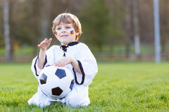 Menino pequeno do fã na visão pública do jogo do futebol ou de futebol Fotografia de Stock