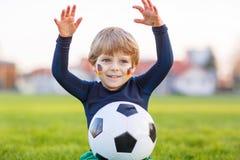 Menino pequeno do fã na visão pública do jogo do futebol ou de futebol Fotografia de Stock Royalty Free