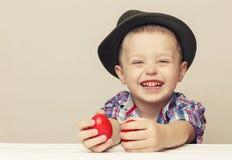 Menino pequeno e bonito da criança de 4 anos em um chapéu e em uma camisa que guardam as mãos Fotografia de Stock