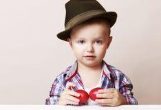 Menino pequeno e bonito da criança de 4 anos em um chapéu e em uma camisa que guardam as mãos Fotos de Stock Royalty Free