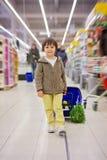 Menino pequeno e orgulhoso bonito que ajuda com as compras na mercearia, saudáveis Imagens de Stock Royalty Free
