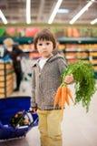 Menino pequeno e orgulhoso bonito que ajuda com as compras na mercearia, saudáveis Fotografia de Stock Royalty Free
