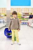 Menino pequeno e orgulhoso bonito que ajuda com as compras na mercearia, saudáveis Imagens de Stock