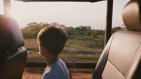 Menino pequeno feliz do turista que aprecia excitando o passeio do por do sol na natureza de exploração do carro da excursão do s filme