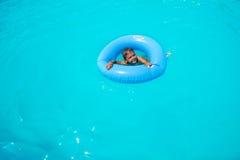 Menino pequeno feliz no anel inflável que nada apenas fotografia de stock