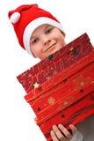 Menino pequeno no chapéu vermelho de Santa que carreg três presentes Imagem de Stock