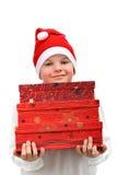 Menino pequeno no chapéu vermelho de Santa que carreg três presentes Foto de Stock