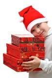 Menino pequeno no chapéu vermelho de Santa que carreg três presentes Fotos de Stock