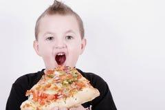 Menino pequeno que come a fatia da pizza Imagens de Stock Royalty Free