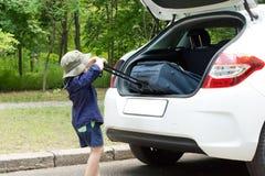 Menino pequeno que esforça-se para carregar sua mala de viagem Imagens de Stock Royalty Free