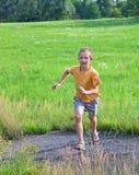 Menino pequeno que funciona no prado verde imagem de stock royalty free