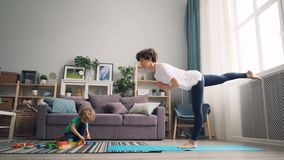 Menino pequeno que joga com blocos quando menina bonita da mãe que faz o equilíbrio da ioga vídeos de arquivo