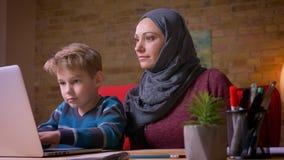 Menino pequeno que joga jogos no portátil e em sua mãe muçulmana no hijab observando sua atividade sentar-se próximo video estoque