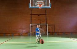 Menino pequeno que joga o basquetebol Fotos de Stock