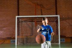 Menino pequeno que pratica saltando um basquetebol imagens de stock