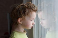 Menino pequeno que senta-se perto da janela e que pensa sobre algo Tem o grande cabelo bonito Bebê bonito fotos de stock