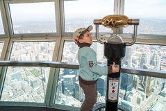 Menino pequeno que usa o telescópio na torre da NC Foto de Stock Royalty Free