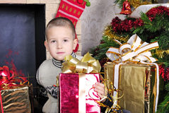 Menino perto de uma árvore de Natal com presentes Foto de Stock Royalty Free
