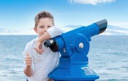 Menino perto do binoscope público do telescópio binocular do scoping próximo fotos de stock royalty free