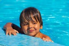 Menino piegas de sorriso que olha felizmente na piscina Fotografia de Stock Royalty Free
