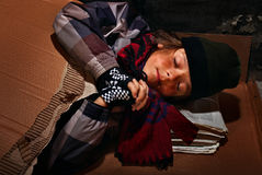 Menino pobre do mendigo que prepara-se para dormir na rua - coberta com fotos de stock royalty free
