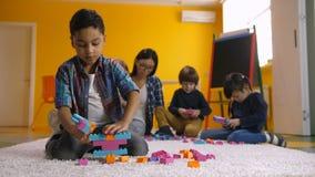 Menino positivo que cria a construção com os tijolos do brinquedo filme