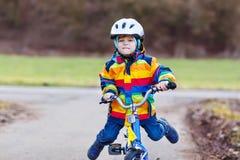Menino pré-escolar bonito engraçado da criança no capacete de segurança e na capa de chuva colorida que montam sua primeira bicic Imagem de Stock Royalty Free