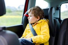 Menino pré-escolar cansado da criança que senta-se no carro durante o engarrafamento Imagens de Stock Royalty Free