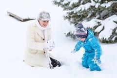 Menino pré-escolar pequeno e sua mãe que jogam com primeira neve em p Foto de Stock