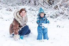 Menino pré-escolar pequeno e sua mãe que jogam com primeira neve em p Fotografia de Stock Royalty Free