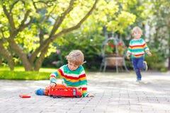 Menino pré-escolar pequeno que joga com brinquedo do carro Fotografia de Stock Royalty Free
