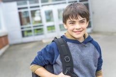 Menino Pre-adolescente agradável fora na escola que tem o bom tempo foto de stock royalty free