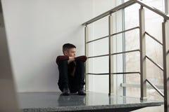 Menino preteen virado que senta-se na escadaria imagens de stock