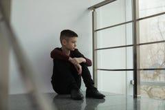 Menino preteen virado que senta-se na escadaria foto de stock