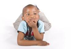 Menino preto dos anos de idade três que encontra-se para baixo sorrindo Fotos de Stock