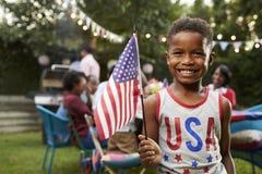 Menino preto novo que guarda a bandeira no partido de jardim da família do 4 de julho Imagem de Stock