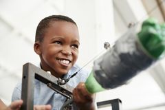 Menino preto novo que usa o foguete da pressão de ar no centro da ciência imagens de stock