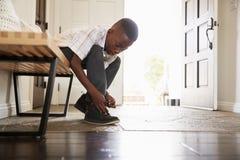 Menino preto pre-adolescente da opinião de baixo ângulo que amarra suas sapatas antes de sair da casa, foco seletivo fotos de stock